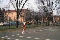 An Augsburg women's tennis team player jumping to serve, circa 1979