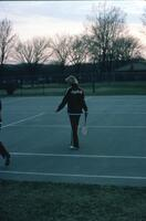 An Augsburg women's volleyball coach standing on the court and holding a racket, circa 1979