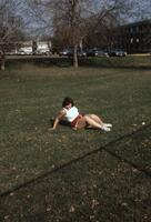 An Augsburg women's track and field team player laying on the grass, circa 1979