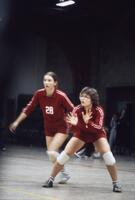 A pair of Augsburg women's volleyball team players moving to intercept a volleyball, November 1979