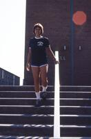 An Augsburg women's volleyball team player walking down the stairs, circa 1978