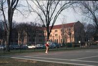 An Augsburg women's tennis team player raising her racket on a court in Winona, circa 1979