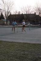 An Augsburg women's tennis team player walking to the net to shake hands, circa 1979