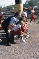 Augsburg women's softball team coach and bench players during a game, 1981.