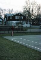An Augsburg women's tennis team player returning an incoming tennis ball, circa 1979