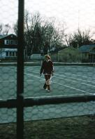 An Augsburg women's tennis team player walking across the tennis court, circa 1979