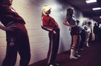 Augsburg women's track and field team lined up inside near a wall, April 1979