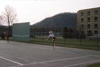 An Augsburg women's tennis team player swinging her racket, circa 1979