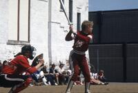 An Augsburg women's softball player batting with catcher ready, May 1983