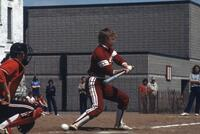 An Augsburg women's softball player swings a strike, May 1983