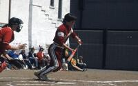 An Augsburg women's softball player running after hitting ball, May 1983