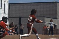 An Augsburg women's softball player swinging, May 1983