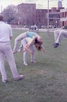 An Augsburg women's track and field team runner holding up another teammate with back, May 1983