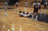 An Augsburg women's basketball player and rival player on the floor, February 1983