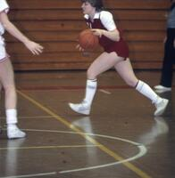 An Augsburg women's basketball player runs while dribbling, February 1983