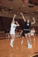An Augsburg women's basketball player and rival player jump for ball, February 1983