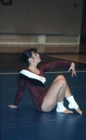 An Augsburg women's gymnastics team member sitting during floor routine, February 1983