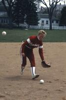 An Augsburg women's softball player reaches to pick up ball, May 1983