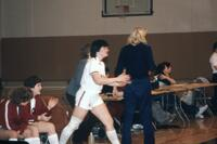 An Augsburg women's basketball player walks from sidelines, February 1983