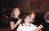 An Augsburg women's basketball player and rival players look over, February 1983