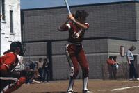 An Augsburg women's softball player at bat ready to swing, May 1983