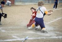An Augsburg women's softball player slides to home plate, April 1983