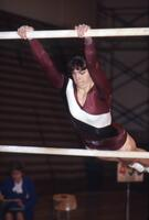 An Augsburg women's gymnastics team member swinging on uneven bars, February 1983