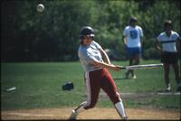 An Augsburg women's softball team player swings at a ball, 1985.