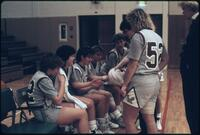 Augsburg women's basketball team players sit on the bench, 1985.