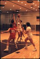 An Augsburg women's basketball team player takes a shot in front of a defenders, 1986.