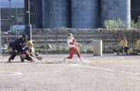 An Augsburg women's softball team player swings her bat at a ball, 1986.