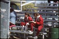 Augsburg women's softball team coaches sit on the bench and take notes, 1985.