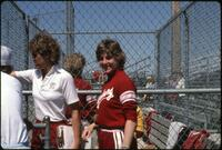 Augsburg women's softball team players sit on the bench and watch a game, 1985.