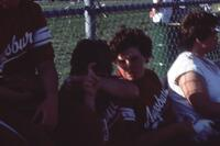 Augsburg women's softball team players on the bench watch a game, 1985.