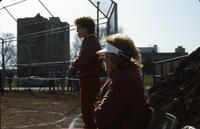 Augsburg women's softball team players sit on the bench, 1984.