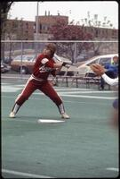 An Augsburg women's softball team player swings at the ball, 1985.