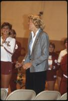An Augsburg women's basketball team coach smiles during senior night, 1985.