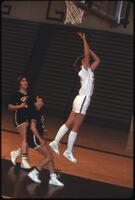 An Augsburg women's basketball team player jumps up for a layup, 1984.