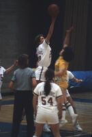 An Augsburg women's basketball team player jumps for the jump up for the ball, 1984
