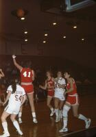 An Augsburg women's basketball team player goes for a rebound, 1984