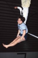 An Augsburg women's gymnastics team member flips over a pull up bar, 1984.