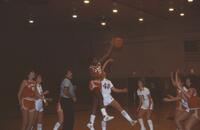 An Augsburg women's basketball team player jumps up for a jump ball, 1984.