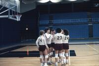 Augsburg women's volleyball team players huddle up, 1985.