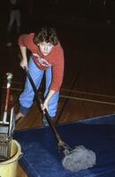 An Augsburg women's gymnastics team member mops the floor mats, 1984.