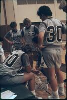 Augsburg women's basketball players surround bench, 1988