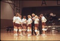 Augsburg women's volleyball team stand around coach, 1987
