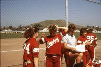 Augsburg women's softball players by fence, April 1987