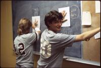 Augsburg women's softball players by a blackboard, May 1988