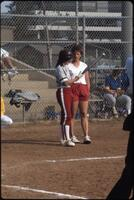 Augsburg women's softball batter talks with woman in shorts, 1988