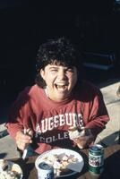 Augsburg women's softball player eating sandwich, May 1988